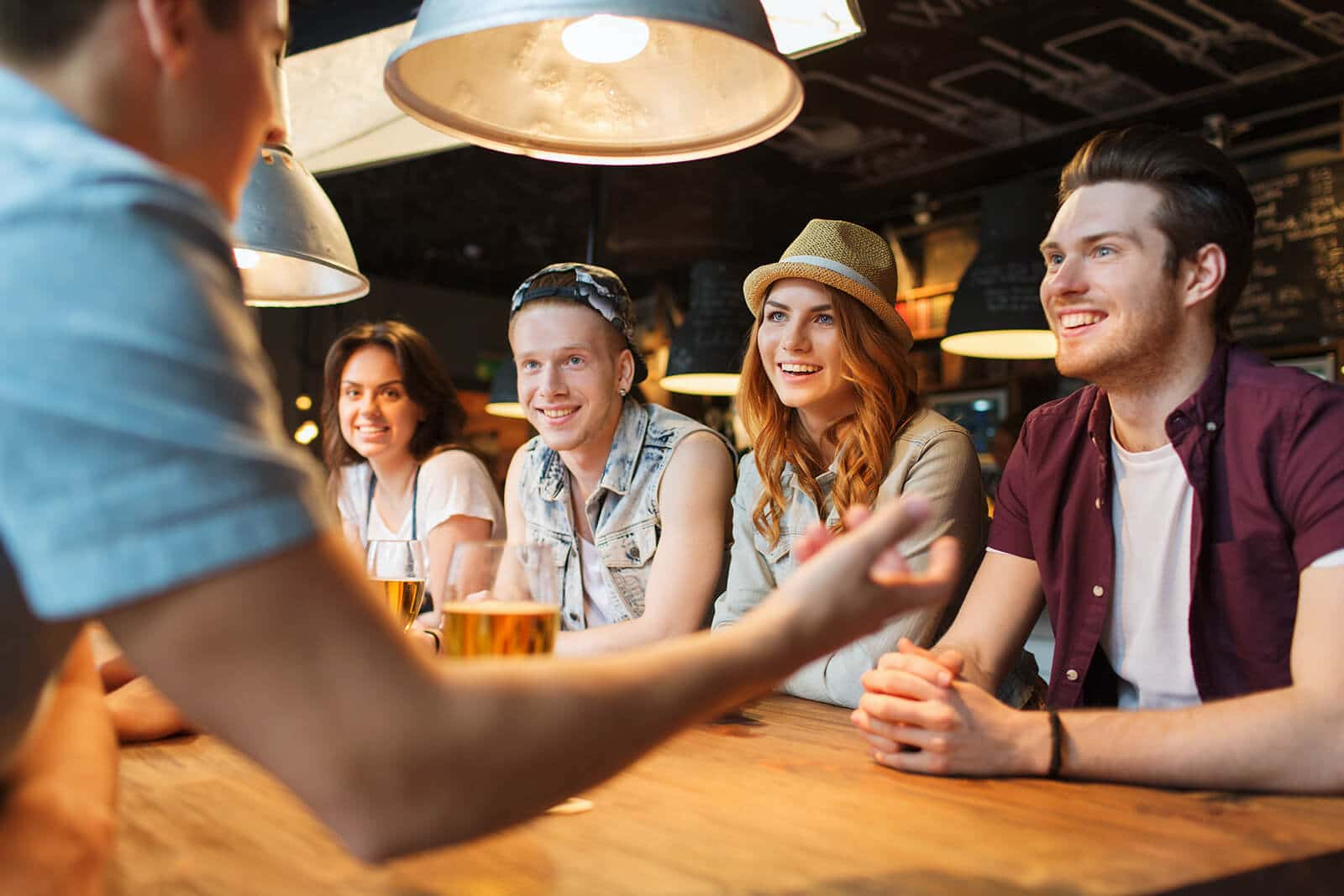 people, leisure, friendship and communication concept - group of happy smiling friends drinking beer and talking at bar or pub